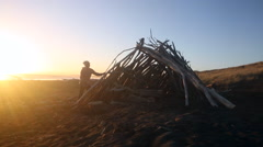 Man adding driftwood to hut on beach at sunset Stock Footage