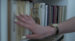 Hand of woman selecting a book from book shelf Stock Footage