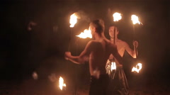 Fire show performance. Three male fire performers dance twirl fire batons staff - stock footage