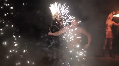 Fire show performance. Male fire performer hold sparkling fireworks poi in teeth Stock Footage