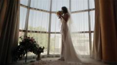 Bride face blurred standing near window smelling wedding bouguet. Tilt shift Stock Footage