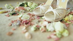 Pair of high heels white shoes lace sandals stand on carpet with rose petals Stock Footage