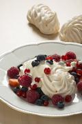 Meringues with fresh berries - stock photo