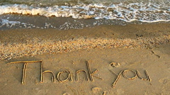Thank you handwritten in sand on a beach - stock footage
