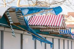 Torn fabric awnings over the closed seaside shops in the offseason Stock Photos