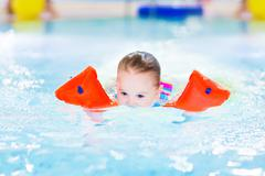 Cute toddler girl swimming in a pool with her face underwater Stock Photos