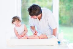 Cute newborn baby looking at his father and toddler sister changing his diaper Stock Photos