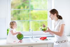 Young mother and her cute toddler daughter cooking together in a sunny kitchen - stock photo