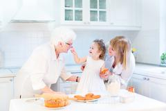Funny toddler girl playing in a kitchen, having fun baking an apple pie Stock Photos