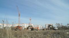 Excavator loads the clay into orange dump trucks Stock Footage