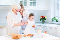 Stock Photo of Happy young woman baking a cake with her senior mother and cute toddler girl