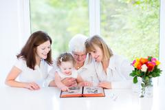 Happy grandmother watching black and white photo album with her family - stock photo