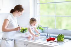 Young mother and her adorable toddler daughter cooking salad - stock photo