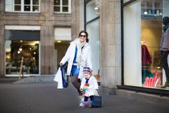 Happy young mother and her toddler daughter enjoying shopping in a city mall - stock photo