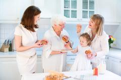 Four generations of women having fun together baking an apple pie - stock photo