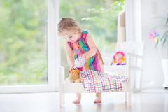 Cute curly toddler girl feeding her toy bear in a white crib - stock photo