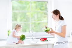 Young mother and her cute toddler daughter cooking together a healthy salad Stock Photos