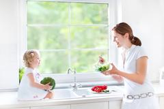 Young mother and her cute toddler daughter cooking a healthy salad Stock Photos