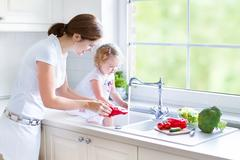 Young beautiful mother and her cury curly toddler daughter washing vegetables - stock photo