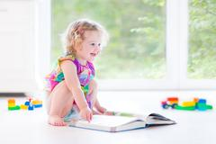 Cute toddler girl reading book sitting on the floor in sunny bedroom - stock photo