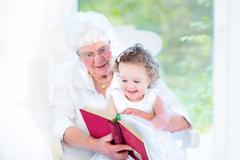 Beautiful senior lady reading a fairy tale book to her little granddaughter Kuvituskuvat