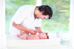 Young happy father playing with his newborn baby son while changing diaper Stock Photos