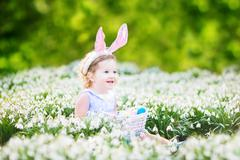 Beautiful toddler girl wearing bunny ears playing with Easter eggs in flowers - stock photo