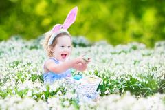Adorable toddler girl wearing bunny ears playing with Easter eggs Stock Photos