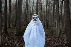 Evil clown in a dark forest in a white veil Stock Photos