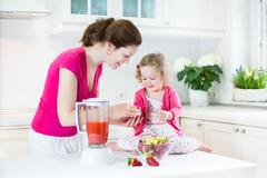 Laughing toddler girl and her mother making fresh fruit juice for breakfast Stock Photos