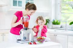 Toddler girl and beautiful mother making fresh strawberry juice for breakfast Stock Photos