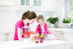 Nice toddler girl and her mother making fresh strawberry juice for breakfast - stock photo