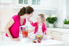 Toddler girl and her young mother making fresh strawberry juice for breakfast - stock photo