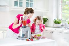 Sweet toddler girl and her mother making fresh strawberry juice for breakfast Stock Photos