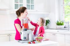 Funny toddler girl and her mother making fresh strawberry juice for breakfast - stock photo