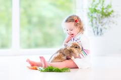 Funny toddler girl hair wearing a white dress playing with a real bunny - stock photo