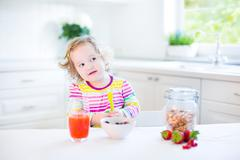 Sweet toddler girl drinking juice and eating corn flakes with strawberry - stock photo