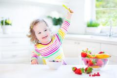 Beautiful toddler girl drinking juice and eating corn flakes with strawberry - stock photo