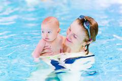 young active woman enjoying swimming pool with a baby boy - stock photo