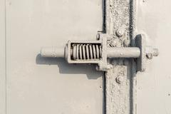 Close up a gray painted spring bolt with metal bolts and plate joins. - stock photo