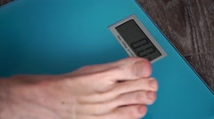 Men's feet on weight scale Stock Footage