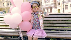 Little cute girl dark hair fashion style clothes dress for kid hold pink and whi Stock Footage
