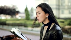 Beautiful young brunette woman read a book in the park wind blew her hair, outdo Stock Footage
