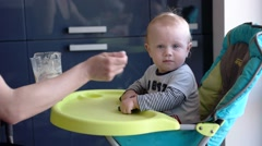Mother Feeding Baby Son in High Chair in Kitchen Stock Footage