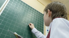 School boy solves math on the blackboard at primary school, 4k shot - stock footage