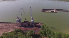 Large crane loading transporting trucks from river barges Stock Footage
