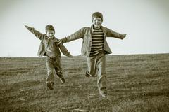 Two boys running together on meadow, sepia toned - stock photo