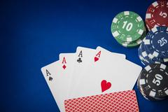 Gambling chips and poker card on blue felt background - stock photo