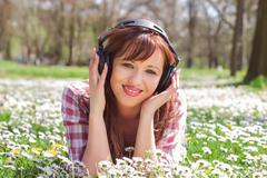Cheerful young woman listening music with headphones and relaxing at beautifu - stock photo