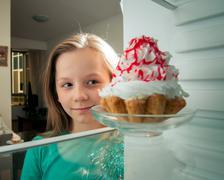 girl sees the sweet cake in the fridge - stock photo
